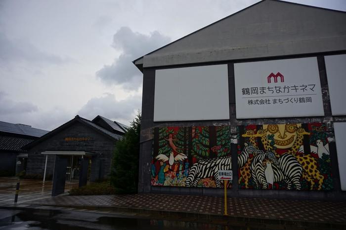 昭和初期建築の木造工場をリノベーションして造られた「鶴岡まちおかキネマ」。木のぬくもりが感じられる昔懐かしい佇まいです。まちなかのオアシス的空間になっています。