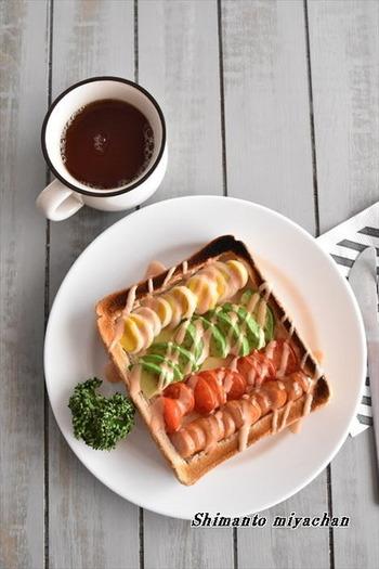 プチトマトやアボカド、うずら卵などビタミンカラーの食材を、パンの上にきれいにレイアウトしてトースト。食パンの耳の際に切り込みを入れて、パンの白い部分を押して少しくぼませることで具材を安定して配置することができます。とてもきれいで、朝から気分が上がりそう♪