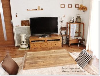 家具をナチュラルな色調で合わせた、統一感のあるリビングルーム。冷たい印象の家電も、ガラスの戸棚を横に配置することで柔らかな雰囲気に。