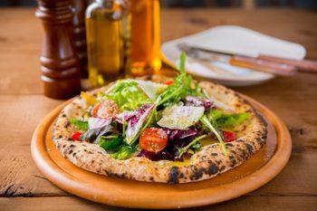 職人わざの光る看板メニューの10種野菜のピザ。 本場イタリアさながらの生地に、旬菜を惜しみなく盛りつけた食べ応え充分のひと品。