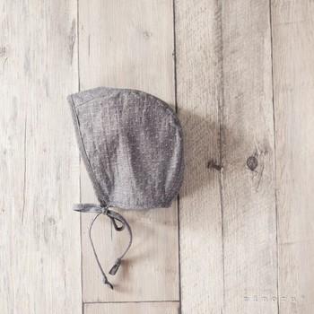 あごひも付きのレトロでキュートな帽子。シンプルなグレーは赤ちゃんのお顔によく似合いますね。