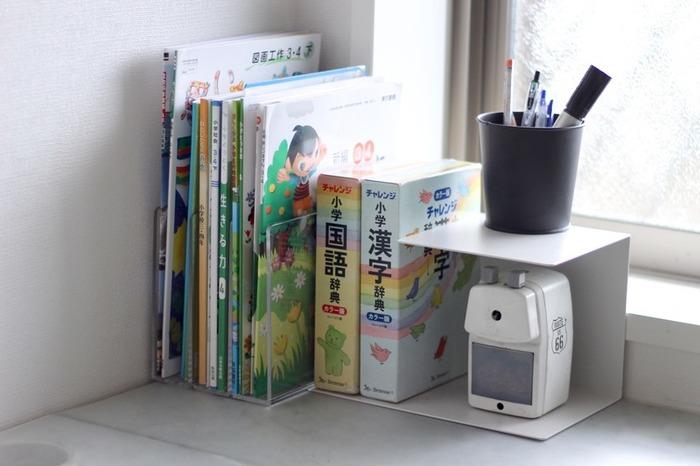 学習机の整理に。左側を本立てに、右側は2段のオープン棚にして、ペンスタンドと鉛筆削りを配置。本はブックエンドで押さえたほうが安定するようです。