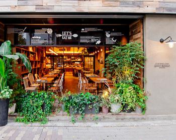 観や内装がとにかくこだわり抜かれていておしゃれ。店先にはたくさんの植木が並び、テーブルや椅子もウッド調でぬくもりのある雰囲気です。