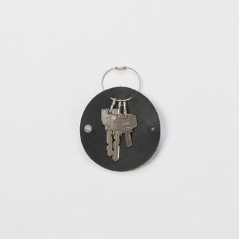 バッグの中のものを傷つけたり引っ掛けたりすることがないように、鍵類はカバーしたいもの。こちらは、キーリングとキーケースの中間のような存在。丸く裁断した革の中に鍵を入れてくるんでボタンで止められる斬新なデザイン。取っ手の部分も華奢でオシャレ度高めです!
