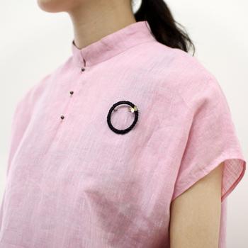 胸元につけると、個性的な異素材の組み合わせが魅力を発揮しています。シャツのボタンの色とブローチの色とあわせれば、ぐっとおしゃれ上級者のコーデに。