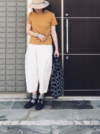 マスタードカラーのLin francais d'antanのTシャツを、見た目も素材も気持ちの良い白パンツに合わせて。ミナペルホネンのバッグをコーデのポイントに。