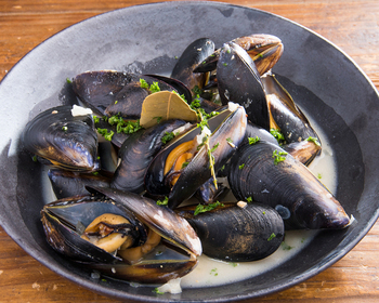 アサリの酒蒸しをムール貝にアレンジした1品。ムール貝料理の際は貝と同系色のお皿を選び、アサリの酒蒸しの場合はアサリと同系色のお皿に盛れば、品の良い質感が演出でき、大人な盛り付けに仕上がります。