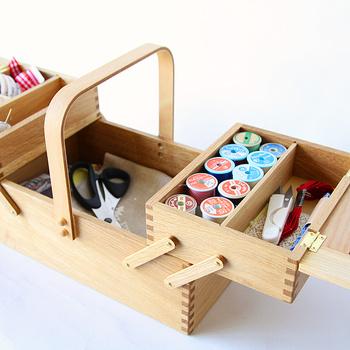 """木のぬくもりに、どこか心が""""ほっこり""""する倉敷意匠の北欧風お裁縫箱。 素材には、国産のナラ材を使用。伝統的な木工技術の「石畳組み接ぎ」の美しさと、丸みを帯びた取手が可愛らしいアイテムです。 こちらのソーイングボックスは、北欧の伝統的なお裁縫箱の使いやすさをそのまま活かした二段式の構造になっていて、上段が左右立体に全開に開き、中身をひと目で確認することができ、お目当ての裁縫道具も見つけやすいようになっています。  開閉がスムーズなのは勿論、開いた状態でもしっかりとした安定感があり、まさに、職人技を感じさせる逸品。 自分の代だけでなく、次の家族へと受け継いで行きたくなる裁縫道具。なんだか、針仕事が楽しい時間になりそうですね。"""