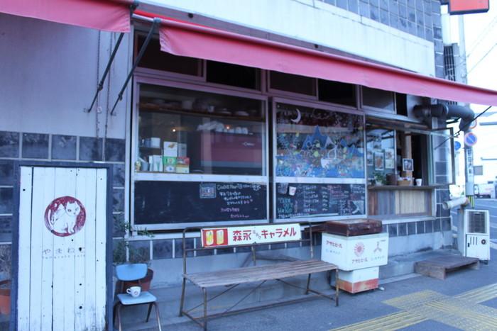 尾道駅南口を出て少し歩いたところにある古ビルの1Fを改装して作られたカフェ。  ネコの看板と昭和雑貨が集まったエントランスが目印です。