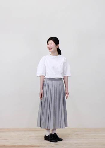 白Tシャツを上品な印象にしたいときは、ロング丈のプリーツスカートを選んで。意外性のある組み合わせが、装いの完成度を底上げします。