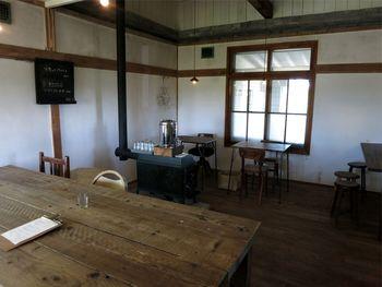 ゆったりとした空間に、すりガラスや梁、薪ストーブなど、古民家ならではの内装が落ち着ける店内。窓の外には一面の大豆畑が広がっています。