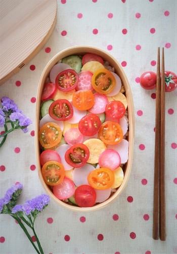 ミニトマトの赤、卵の黄色、きゅうりの緑、ハムのピンクなど、色とりどりの食材を輪切りや丸く型抜きした具材を散らした水玉ちらし。コントラストが美しく、しかもヘルシーな大人の女性におすすめの魅せ弁当です。