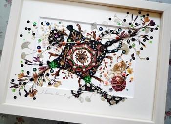 セージやカスミソウなどの押し花と、和紙やスワロフスキーを組み合わせた、アンティークな雰囲気漂う抽象的な作品です。