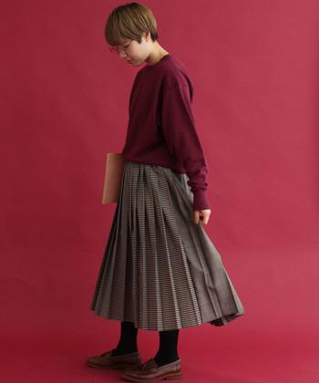 シックなボルドーニットに、細かなチェックのプリーツスカートを合わせた女性らしいコーディネート。落ち着いた色合いで、ふわりと揺れるプリーツスカートが知的な印象に見せてくれます。