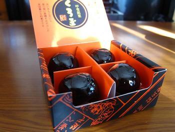昭和4年から販売されている「くろ玉」。青えんどう豆だけで作るうぐいす餡が黒糖羊羹で包まれていて、つややかな黒がシックで上品です。黒とオレンジの個性的なパッケージも印象的。