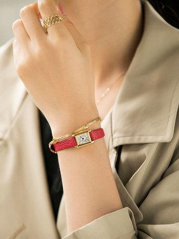 赤いバンドの時計もそれだけでコーデのアクセントになりますね。文字盤の周りのゴールド、バングルのゴールド、そして指輪のゴールドとまとまり感があって手元がとても綺麗に見えますね。