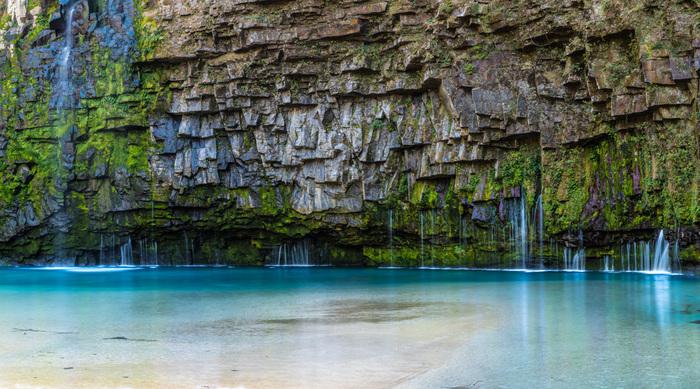 楽園を思わせるコバルトブルーの水に、地球の歴史を感じる不思議な地形。鹿児島県の南大隅町を流れる雄川上流にある雄川の滝(おがわのたき)は、落差46m幅60mの滝です。 駐車場から約1,200mの遊歩道を歩きながら、滝つぼを目指しましょう。