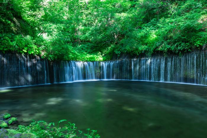 避暑地・軽井沢の白糸の滝は、水が幅広い岩肌を伝い糸のように細く流れ落ちていく繊細で優美な滝。少しだけ都会を離れて、マイナスイオンあふれる幻想的な世界で新鮮な空気をたっぷり味わってみませんか?