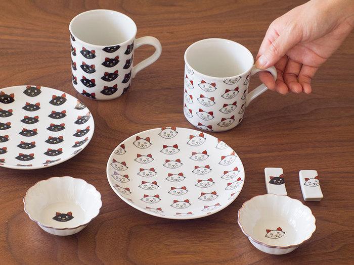 """「九谷焼をみなさんの身近に」をテーマに、転写技術を使ったワークショップや製品を企画している""""KUTANI SEAL""""からは、 とぼけた表情が可愛い子猫シリーズを紹介します。丸皿とマグカップには、スペースいっぱいに猫のイラストが…。マグカップの底を覗くと、子猫の底にはネズミ、黒猫の底にはお魚の絵柄が施され、思わずほっこり笑顔に! 小鉢と箸置きには、控えめなワンポイント使いの猫が顔をのぞかせ、いつもの食卓に賑やかで楽しい雰囲気をプラスしてくれます。"""