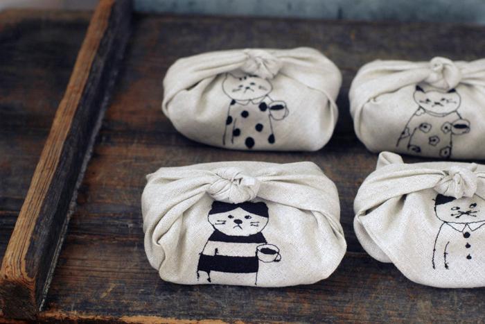"""ユニークな猫の刺繍がひときわ目を引く、リネン素材のお弁当包みは、ミシン刺繍作家の菅原しおんさんと倉敷意匠計画室のコラボアイテム。ミシンの上糸と下糸の調子が合わない時に生じる""""糸溜まり""""を意図的に表現し、描かれる猫のキャラクターに適度なゆるさプラスされています。"""