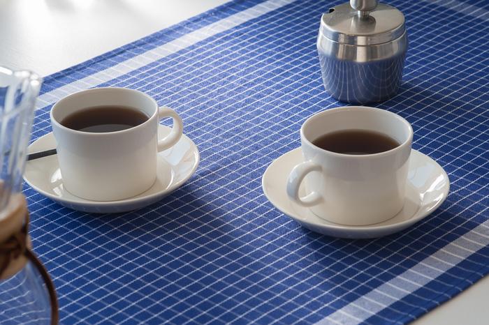 真っ白なうつわの下には、きっちりとアイロンのかかったブルーのクロスを敷きこんで。まるで老舗の喫茶店のテーブルクロスのように整えられた印象です。