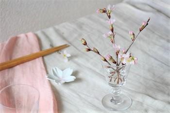 工夫次第で、ガラスの脚付きグラスにも枝ものを飾ることができます。ひと枝だけではひっくり返ってしまいがちなので、いくつかクロスさせて、それぞれで枝を支えるようにしています。