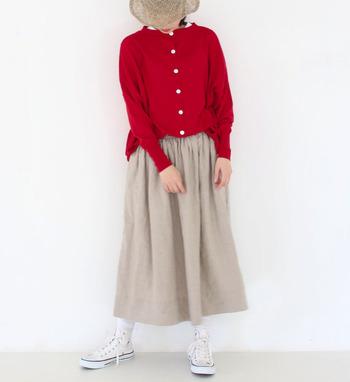 赤のカーディガンに、ベージュのロングスカートを合わせたスタイリング。カーディガンは前のボタンを全部留めて、トップス感覚で着こなしています。白のスニーカーをチョイスした、爽やかな印象のコーディネートです。