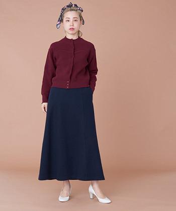季節感のあるボルドーカラ―のカーディガンは、胸元にビスチェのような編地が入っているのが特徴。黒のロングスカートに合わせてカッコよく着こなしています。白パンプスがダークトーンのスタイリングに程よいアクセントをプラス。