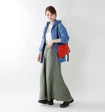 裾が切りっぱなしになったカーキのロングスカートに、デニムのジャケットを合わせたボーイッシュなコーディネート。赤のショルダーバッグをアクセントに使い、クールな中にも女性らしさをしっかり演出した着こなしに仕上げています。