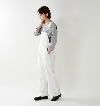カジュアルにもキレイめにも着こなせる白のオーバーオールは、一枚持っていると便利なアイテムです。グレーのシャツと合わせて、かっちりした印象のスタイリングに。