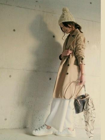 ホワイト×ベージュのコーデで、トレンチを女性らしく着こなしています。袖をまくってもシワになりにくい素材なら安心ですよね。
