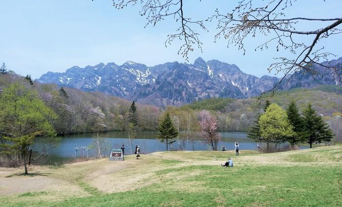 池の手前には公園のような芝生広場があり、本を読んだりお弁当を広げるひとも。(筆者撮影) 池を見おろす高台にはカフェ「鏡池どんぐりハウス」があります。
