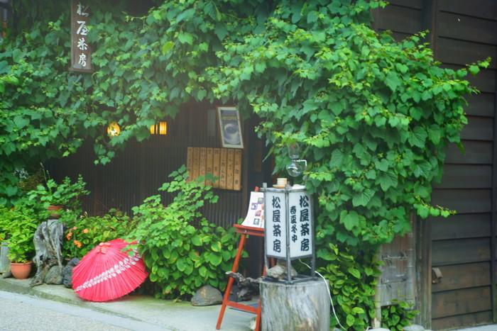 歩き疲れたら、甘いものを食べてひと休みしましょう。奈良井駅から徒歩6分の「松屋茶房」は、外壁を覆う野葡萄のツルと赤い番傘がトレードマークです。建物は江戸末期に建てられたものだそう。
