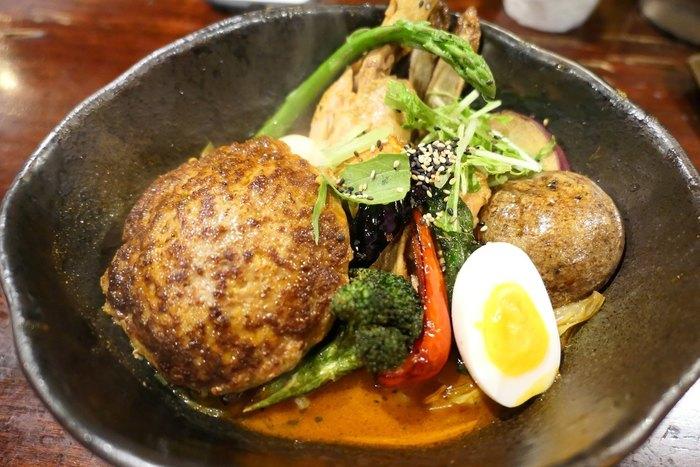 行列必至の人気スープカレー店「奥芝商店」。濃厚でコクのある「海老スープ」に、「宗谷黒牛」「ルスツ産もち豚」など、産地にもこだわったお肉や北海道産野菜がゴロゴロ!一皿で「北海道」をまるごと味わえます。鉄板焼きで焼き上げたハンバーグ「おくしバーグ」が人気です。