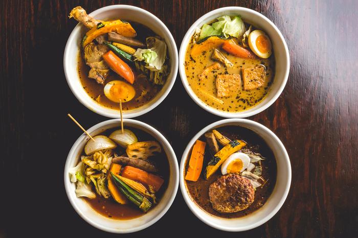『ミシュラン北海道 2017』に紹介された人気のスープカレー店。こちらの特徴は、なんといっても4種類から選べるスープ。スタンダードな「黄」、トマトベースの「赤」、濃く深い「黒」、豆乳がまろやかな「白」。さらに選べる具材&トッピングで組み合わせは無限!思わず何度も通いつめてしまうのです。