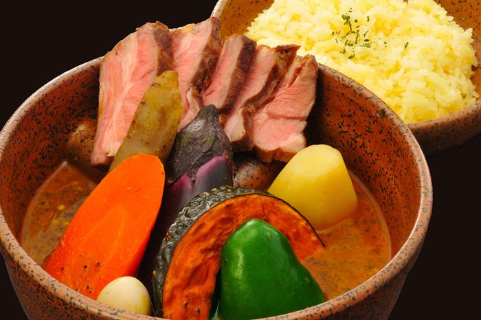 スープカレーのもう一つの特徴は、ゴロゴロの大きな具材。チキンレッグや豚の角煮、ラムチョップなどのお肉をメインに、ナスやかぼちゃ、じゃがいも、ピーマンなどの地元産野菜が加わります。エビやホタテ、牡蠣など、北海道の魚介をメインにするのもアリ。具材でも「北海道」を存分に味わえるのがうれしいですね!