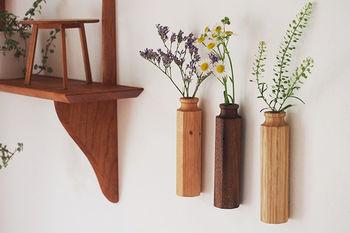 季節の草花を生ける「花器」にもこだわってみると、さらにおしゃれな雰囲気を演出できます。こちらは木のぬくもり溢れる、木製のおしゃれな一輪挿しです。中には試験管が入っているので、生花を生けて飾ることもできます。マグネット式で簡単に壁に取り付けられるので、リビングや寝室など、お家の中の様々な場所で楽しむことができますよ。