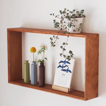 木でできたおしゃれな一輪挿しは、こちらのようにシンプルな棚に飾っても素敵ですよね。ほかの植物やインテリアアイテムと一緒にレイアウトすると、よりおしゃれな雰囲気に。赤い実のついた可愛らしい植物や枝物を飾って、秋らしさを感じるコーディネートを楽しんでみてはいかがでしょうか。