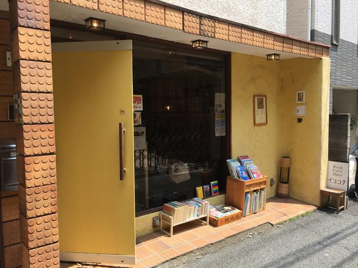 黄色い壁とおもちゃのブロックのようなタイルに囲まれた可愛らしい外観のブックカフェ『イココチ』。 静かな住宅街の中の隠れ家的存在です。