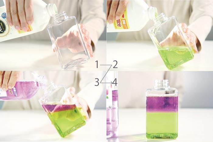 白いボトルのJOY(W除菌)をボトルの壁に沿わせるように、半分注ぎます。 続けて、ゆっくりと透明ボトルのJOYを注いで、完成! 2種類の比重が異なる洗剤だから、色が混ざらずに分かれます。
