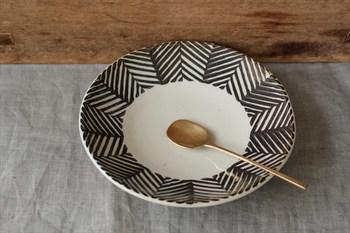 フリーハンドで描かれたヘリンボーン柄が目を惹く丸皿です。いつもの料理をざっくり入れても、どこか絵になるモダンな盛り付けに。