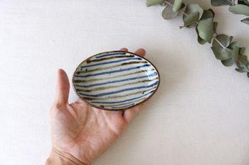 手描きならではの不均一な縞模様で、穏やかな表情の小判皿です。オーバル型の豆皿は、食卓にちょっと変化を付けたいときに重宝しますよ。