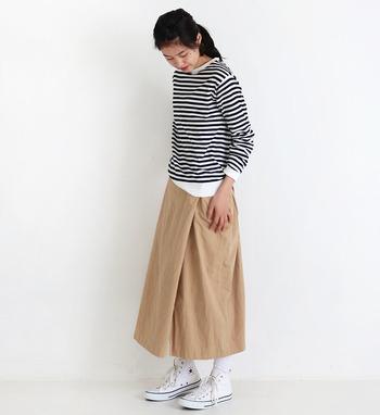 ボーダーのプルオーバーニットに、ちょっぴり濃いめのベージュスカートを合わせたコーディネートです。首元が詰まっているニットは、旬のアイテム。白スニーカーと合わせて、カジュアルな印象にまとめています。