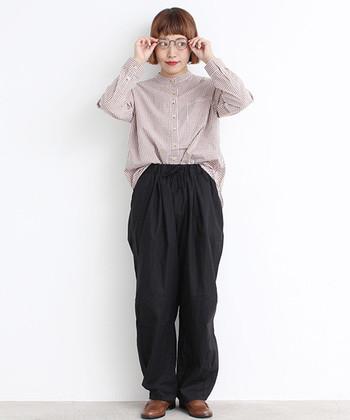 茶色のチェック柄シャツに、ダークトーンのイージーパンツを合わせた着こなし。フロント部分だけをタックインして、パンツのゆるさをアピールできるリラックススタイルです。チェック柄シャツをゆるく着こなしたい時に、ぴったりのスタイルですね。