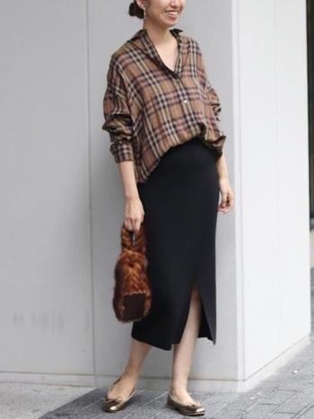 黒のタイトスカートに合わせるなら、タックインした裾を大胆に引き出してトップスにボリュームを持たせましょう。ファーバッグなどの季節感アイテムを取り入れるのもポイントです。