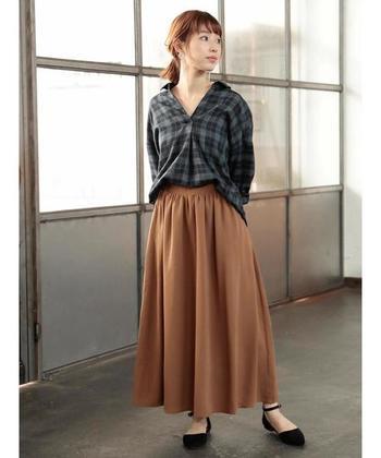 茶色のフレアスカートにチェック柄シャツを合わせるなら、フロント部分だけをタックインする着こなしも◎ふんわりシルエットと揺れで女性らしい秋コーデに仕上がります。