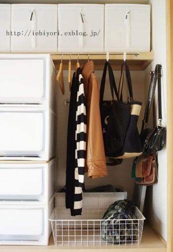 押入れの上段にポールを取付け、大人ものの洋服やバッグを掛けて収納。押入れの壁に取り付けたフックに小さなショルダーを掛けて、空間を有効利用。