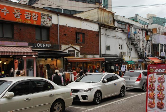 駐車場が道の真ん中にあるという、「駐車場通り」。駐車場の両側には、たくさんのお店がズラリと並んでいるんです。かわいいのにプチプラの洋服がGETできたり、韓国コスメ店、飲食店もたくさんあります。昼過ぎからは屋台も並び、深夜までずっと賑やかな通りです。
