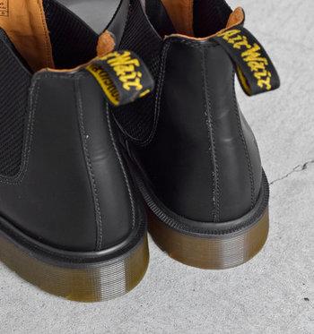 """履き口には、ブラック地にイエローのロゴ刺繍を施したプルストラップが。王道でありながら、細部にはしっかりと""""ドクターマーチンらしさ""""が感じられるデザインです。"""