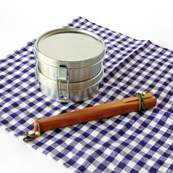 コロンとかわいい丸いお弁当箱は2段弁当。金具でかっちり留められるから、ずれることもありません。中には仕切りもついています。
